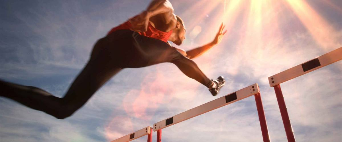 Runner jumping over running hurdle, low angle view