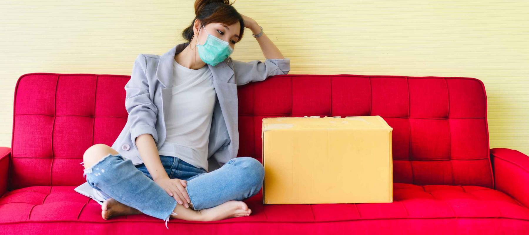 Young woman wearing mask sitting on red couch at home with feeling sad and disheartened from company layoff during covid-19, reduction cost. Pandemic disease and impacts every business.