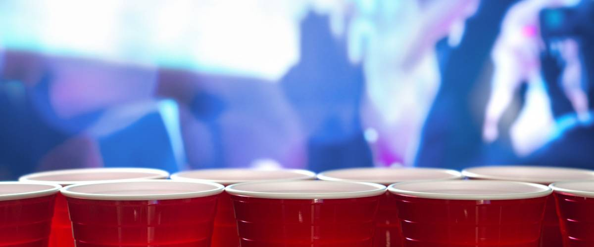 Plastic red party cups in a row in a nightclub full of people dancing on the dance floor in the background.