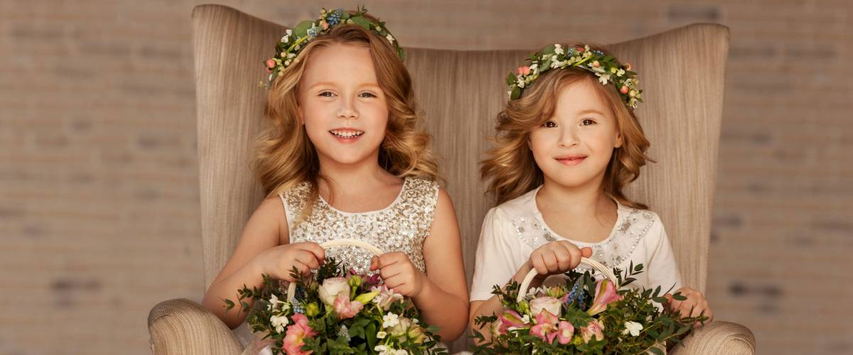 Two little flower girls sitting in a chair with bouquets