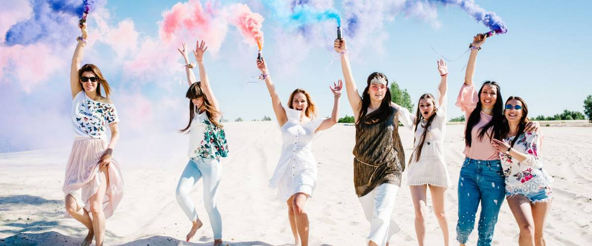 Bridesmaids holding colored smoke bombs for bachelorette party on the beach