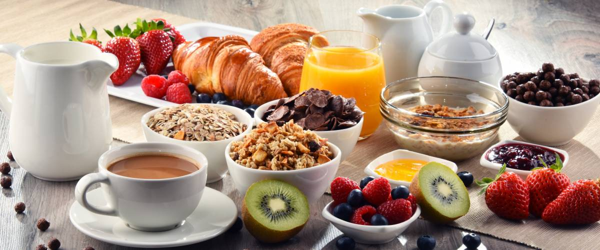 Breakfast served with coffee, orange juice, croissants, cereals and fruits.