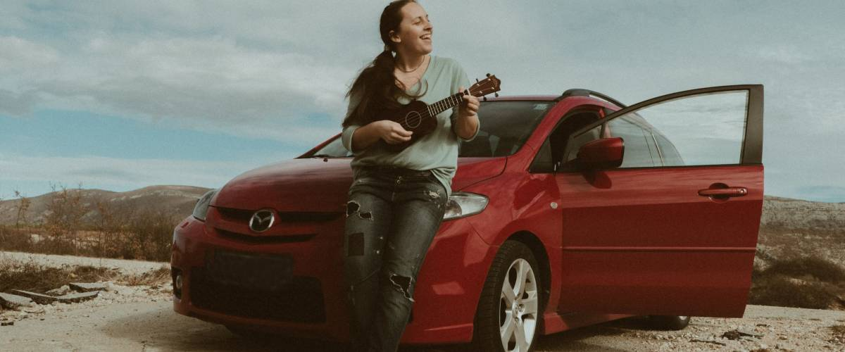 Montenegro - February 6, 2017: young woman in jeans playing the ukulele near Red car Mazda standing on the road near mountains at daytime