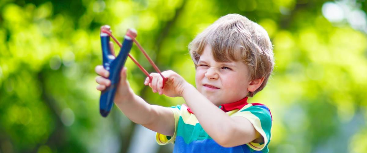 Funny little kid boy shooting wooden slingshot against green tree background. Child having fun in summer. On sunny warm day, active leisure for kids.