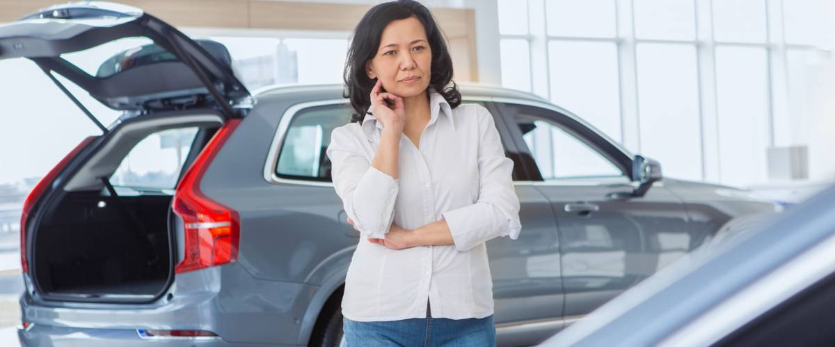 Thoughtful mature Asian woman choosing a car at the dealership. Female customer thinking looking at new cars at the salon copyspace choice deciding buying buyer client consumerism luxury auto