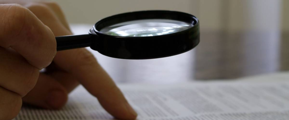 the person reads the document through a magnifying glass at the table