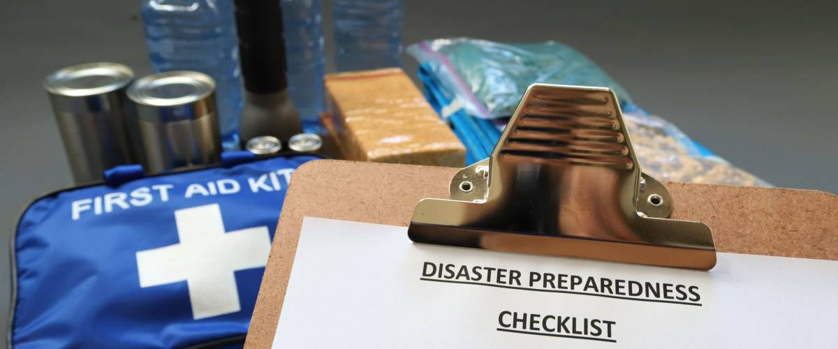 Disaster preparedness checklist and first aid items in background