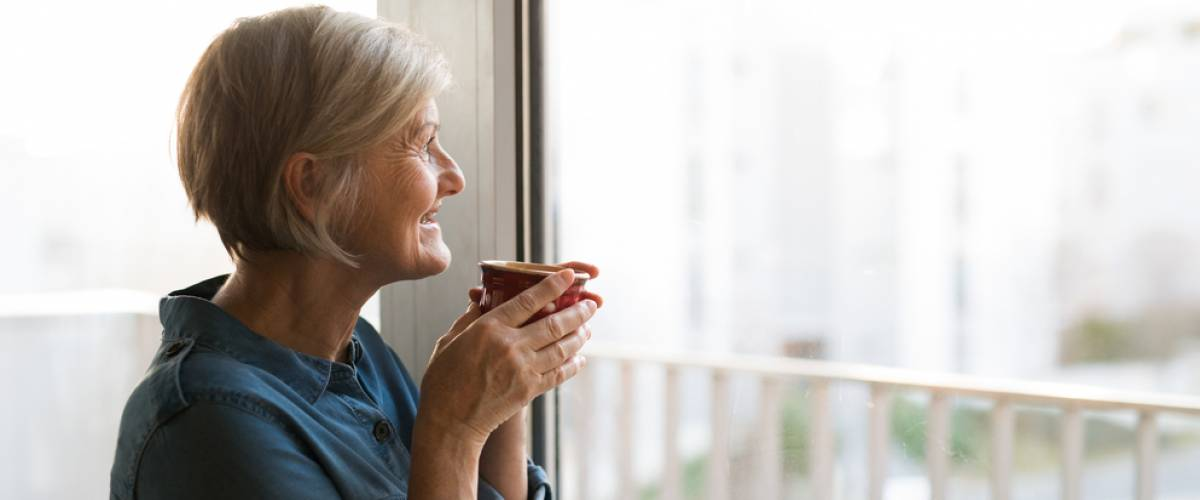 retirement age woman drinking coffee from a mug looking out the window