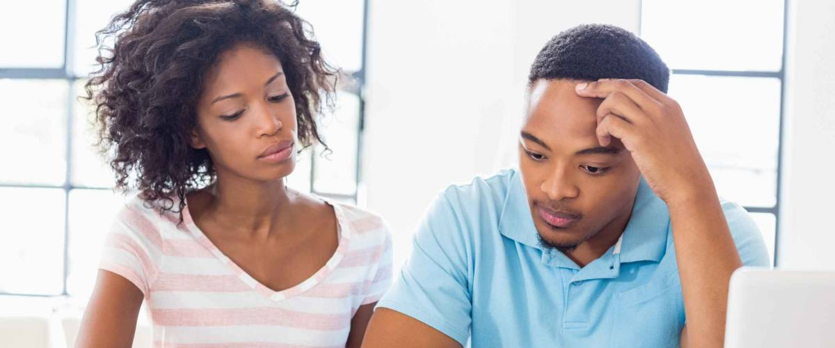Worried young couple discussing bills at home