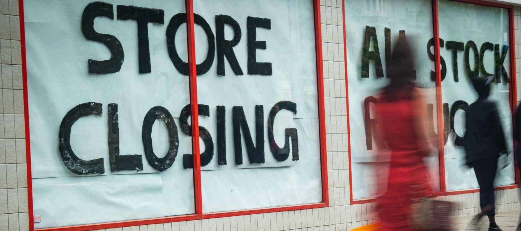 High Street 'Store Closing' sign with motion blurred shopper walking past
