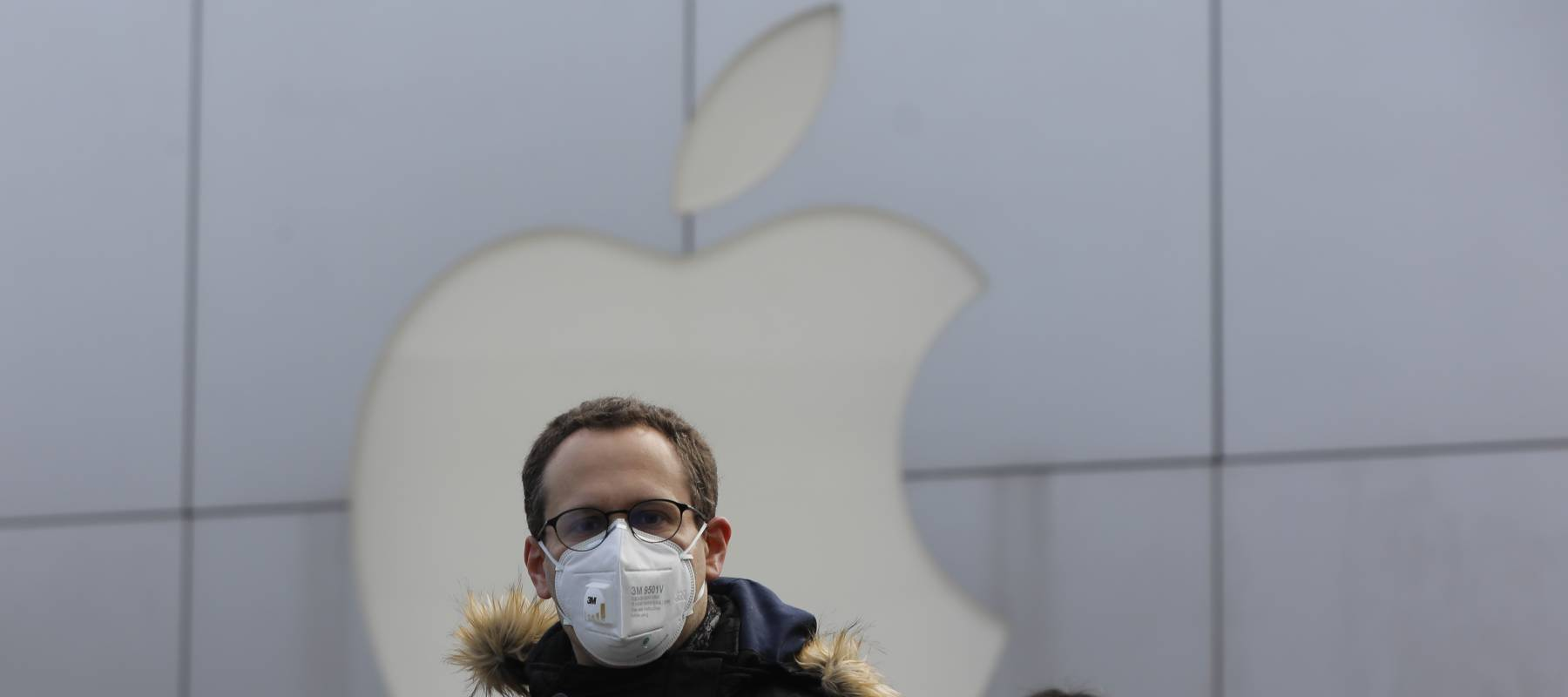 People wear masks as they walk past a closed Apple store at Sanlitun in Beijing, China, 02 February 2020.