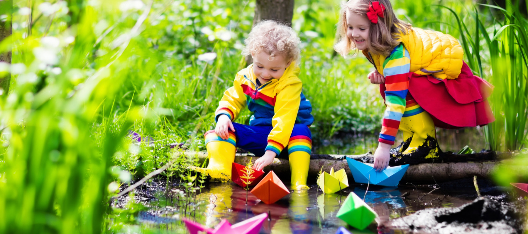 Children play with colorful paper boats in a small river on a sunny spring day.